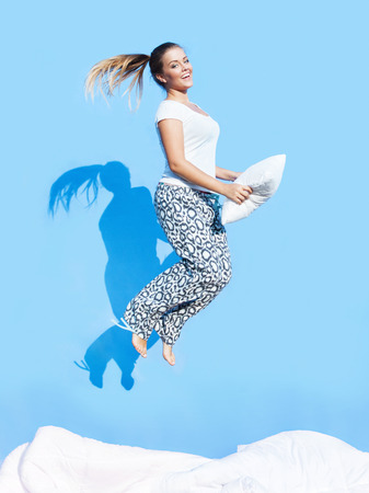 Happy morning concept, woman holding a pillow jumping up on bed photo
