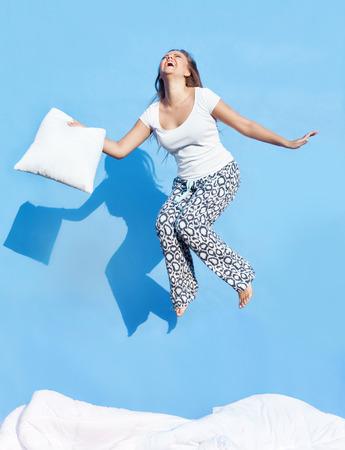 Glücklicher Morgen Konzept, Frau mit einem Kissen sprang auf dem Bett Standard-Bild - 32614373