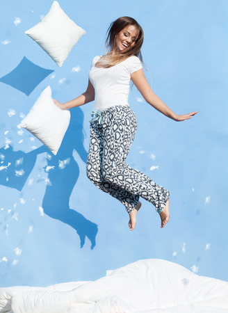 up wake: Happy morning concept, woman holding a pillow jumping up on bed