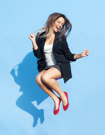 gente saltando: Exitosa joven y atractiva mujer riendo saltando