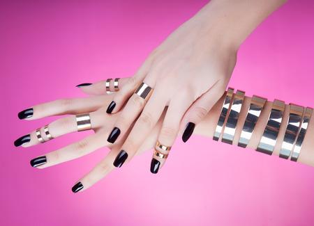 vrouwen: Vrouw met zwarte manicure dragen van gouden armband en ringen Stockfoto