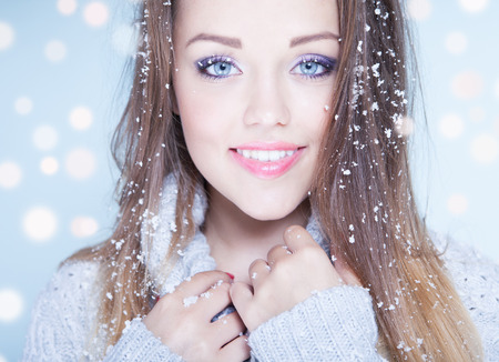 skin color: Winter face close up of young woman covered with snowflakes
