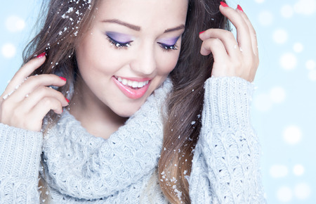 Winter face close up of young woman covered with snow flakes Stock Photo