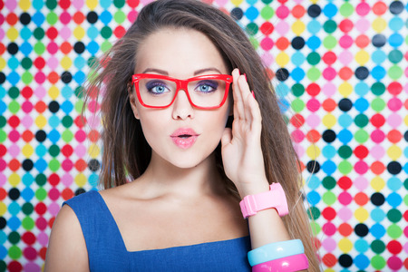 Attractive surprised young woman wearing glasses on spotted background, beauty and fashion concept photo