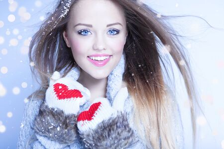 christmas winter: Beautiful happy young woman wearing winter gloves covered with snow flakes. Christmas snowing portrait concept.