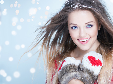 Beautiful happy young woman wearing winter gloves covered with snow flakes. Christmas portrait concept.