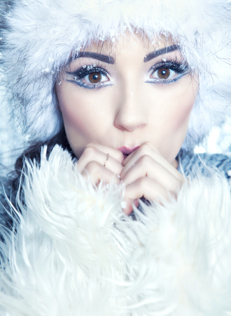 frozen winter: Winter face close up of young attractive woman wearing hat and fur covered with snow flakes. Christmas beauty concept.