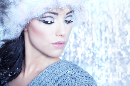 winter fashion: Winter face close up of young attractive woman covered with snow flakes. Christmas concept. Stock Photo