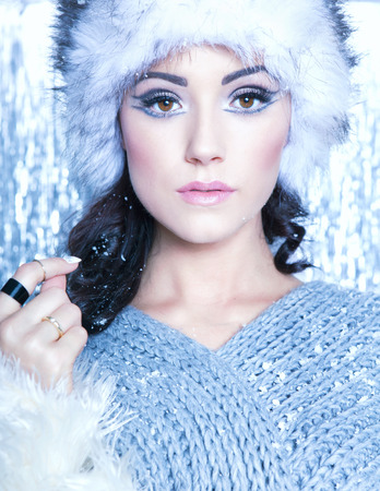 glamour woman: Winter face close up of young attractive woman covered with snow flakes. Christmas concept. Stock Photo