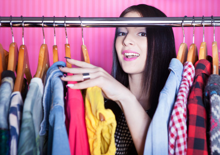 woman searching: Young surprised woman searching for clothing in a closet
