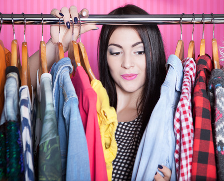 woman closet: Young attractive woman searching for clothing in a closet