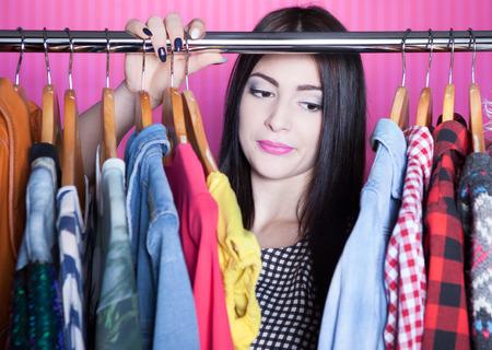 Jonge aantrekkelijke teleurgesteld vrouw op zoek naar kleding