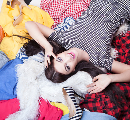 woman closet: Young happy woman lying down on a pile of clothes Stock Photo