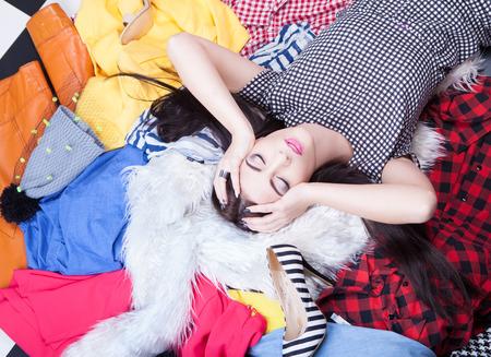 habitacion desordenada: Nada de llevar el concepto, mujer acostada en una pila de ropa Foto de archivo