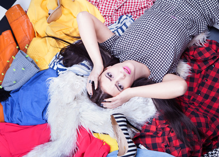habitacion desordenada: Mujer joven tensionada que se acuesta en una pila de ropa Foto de archivo
