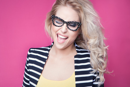 Young attractive happy winking woman wearing glasses