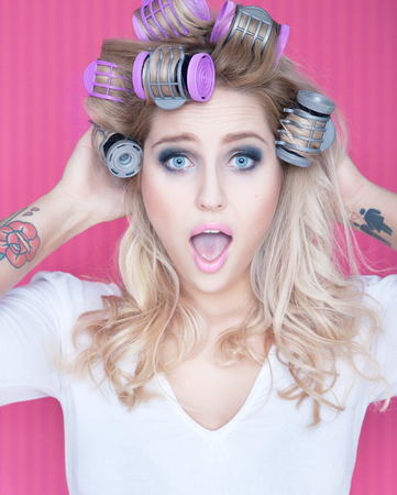 Young attractive surprised woman with hair curlers
