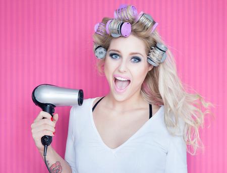 pelo: Mujer atractiva joven con secador de pelo y rizadores