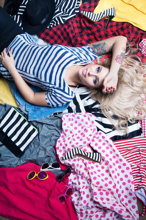 get dressed: Young attractive woman lying down on a pile of clothes