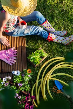 Vrouw die een pauze tijdens het werken in de tuin