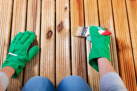 treated board: Applying protective varnish on a patio wooden floor, maintenance concept