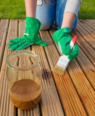 treated board: Applying protective varnish on a patio wooden floor, house improvement concept