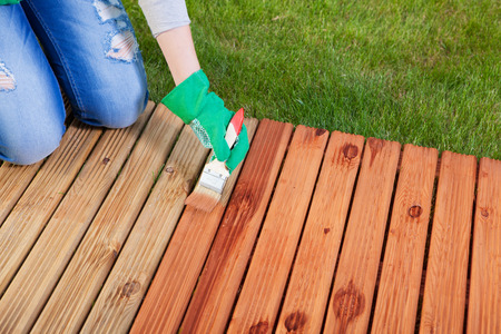 mantenimiento: La aplicación de barniz protector sobre un suelo de madera del patio, el concepto de mantenimiento Foto de archivo