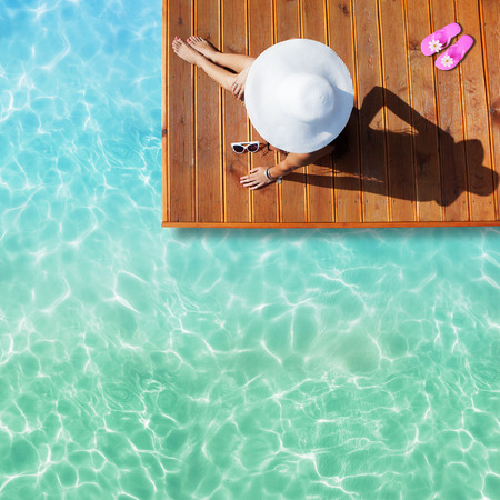 pool: Summer holiday fashion concept - tanning woman wearing sun hat at the pool on a wooden pier shot from above