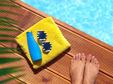 Zomervakantie fashion concept - vrouw op een houten pier bij het zwembad Stockfoto