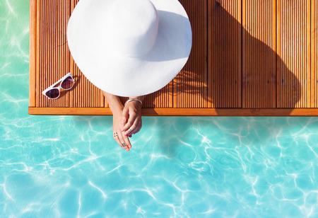 sol: Concepto de moda Vacaciones de verano - bronceado mujer llevaba sombrero de sol en un muelle de madera vista desde arriba Foto de archivo