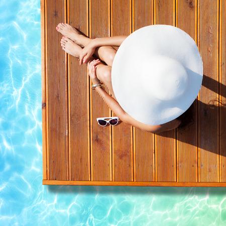 Sommerurlaub Mode-Konzept - Gerbung Frau tragen Sonnenhut am Pool auf einem hölzernen Pier Blick von oben Standard-Bild - 43113274