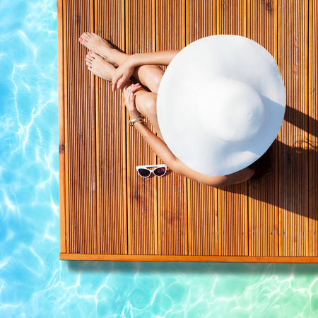 body jewelry: Summer holiday fashion concept - tanning woman wearing sun hat at the pool on a wooden pier view from above