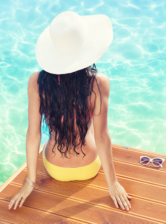 Summer holiday fashion concept - tanning woman wearing sun hat at the pool on a wooden pier