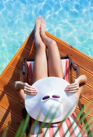 piel humana: Concepto de moda Vacaciones de verano - bronceado mujer que llevaba sombrero de sol en una silla de playa de madera en la vista a la piscina desde arriba