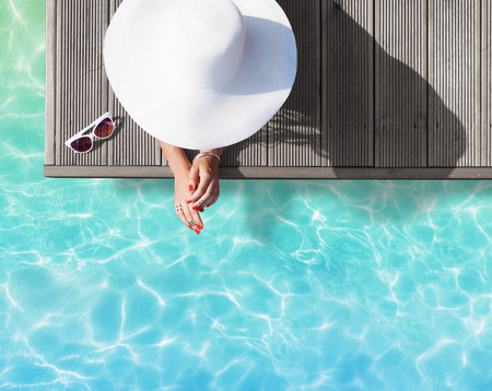 pool deck: Summer holiday fashion concept - tanning woman wearing sun hat on a wooden pier view from above
