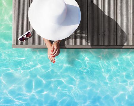 moda: Verão conceito fashion feriado - curtimento mulher vestindo chapéu de sol em um cais de madeira vista de cima