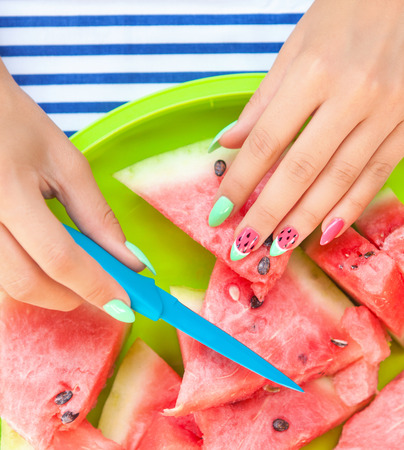 water melon: Hands close up of young woman with watermelon manicure cutting watermelon fruit, summer manicure nail art and food concept Stock Photo