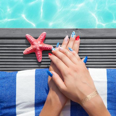 marinero: Mujer acostada en la piscina, uñas de gel marinero marina close up concepto de belleza verano