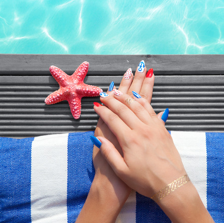 sailor: Woman lying down by the pool, marine sailor gel nails close up summer beauty concept