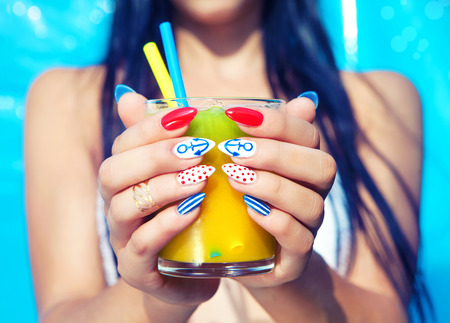 Young woman with marine sailor manicure holding glass of orange juice, summer nail art beauty and drink concept photo