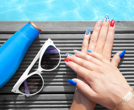 Woman lying down by the pool, marine sailor gel nails close up summer beauty concept