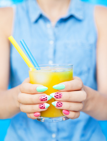 Hands close up of young woman with watermelon manicure holding glass of orange juice, manicure nail art concept Stock Photo