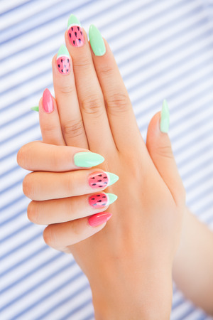 Hands close up of young woman with watermelon manicure summer  nail art  concept Archivio Fotografico