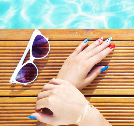 Woman lying down by the pool, marine sailor gel nails close up summer beauty concept 版權商用圖片 - 43150956