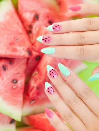 manicura: Manos cerca de la mujer joven con la manicura sand�a y fruta, arte de la manicura de u�as de verano y concepto de la comida