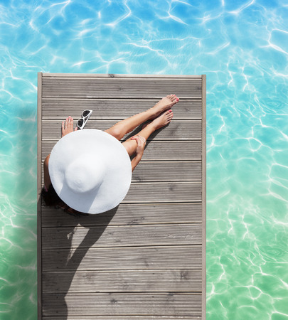 Summer holiday fashion concept - tanning woman wearing sun hat at the pool on a wooden pier view from above