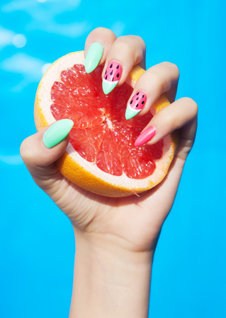 Hands close up of young woman with watermelon manicure holding slice of grapefruit summer manicure nail art and food concept