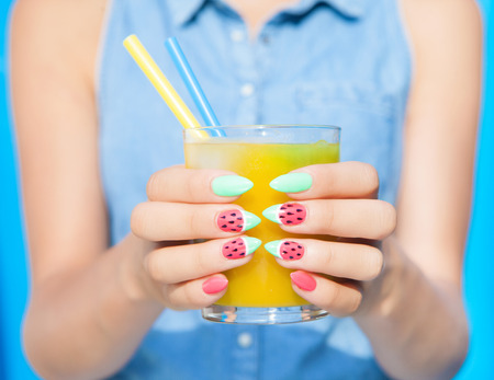 Hands close up of young woman with watermelon manicure holding glass of orange juice, manicure nail art concept Foto de archivo