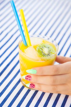 manicura: Manos cerca de la mujer joven con la manicura de la sandía con vaso de jugo de naranja, manicure arte conceptual