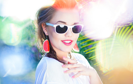 summer beauty: Colorful summer portrait of happy young attractive woman wearing sunglasses and watermelon earrings, beauty and fashion concept natural bokeh and light effect
